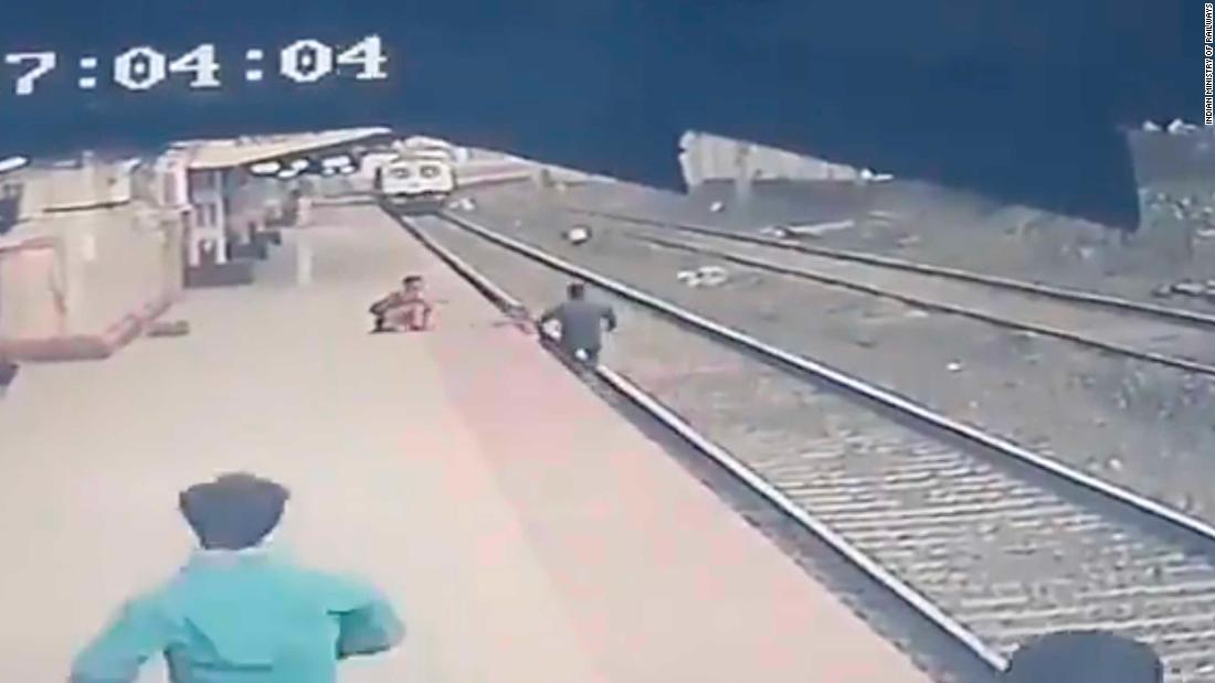 Video shows the moment an Indian railroad worker snatched a child from the path of a train