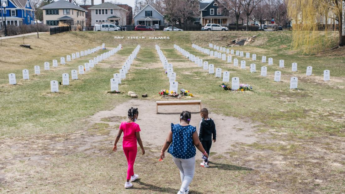 "Children walk at a memorial in Minneapolis on Sunday, April 4. The ""Say Their Names"" symbolic cemetery memorializes Black lives lost at the hands of police."