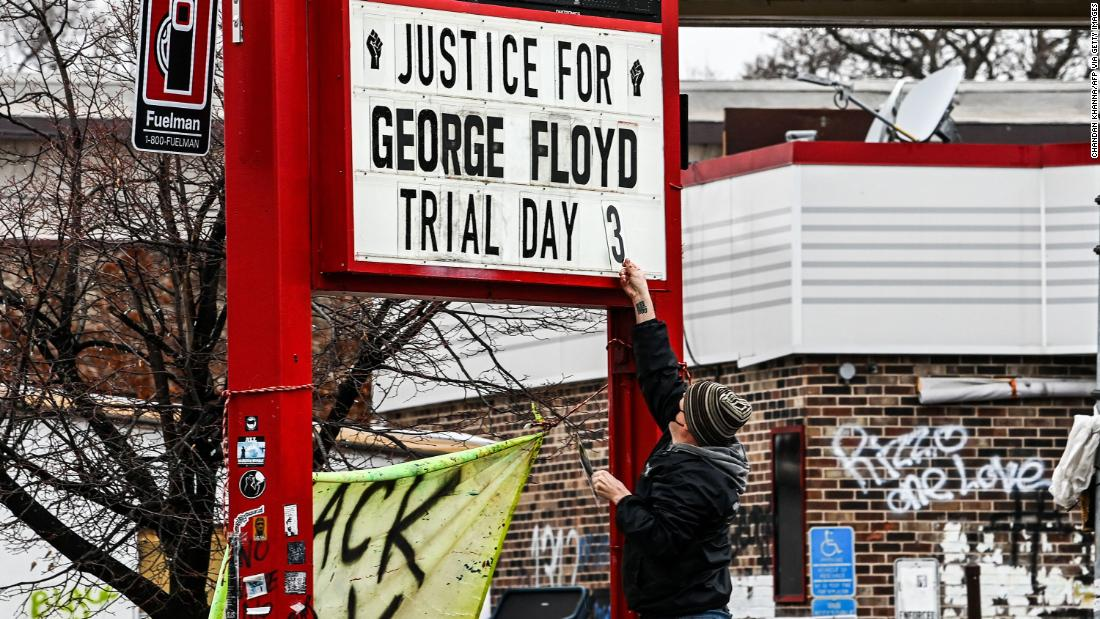A man changes the number of a sign board at a makeshift memorial for Floyd in Minneapolis on March 10.