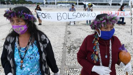 Brazilian indigenous people from various ethnic groups protest against the proposal of the federal government to legalize mining in indigenous lands, in front of Planalto Palace in Brasilia on April 19, 2021.