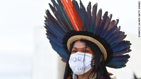 An indigenous woman takes part in a protest along with people from various ethnic groups in a protest against the proposal of the federal government to legalize mining in indigenous lands, in front of Planalto Palace in Brasilia on April 19, 2021. - As Indigenous Day is celebrated in Brazil on April 19, the protesters criticized the policies of President Jair Bolsonaro's government and the withdrawal of their rights guaranteed in the constitution. (Photo by EVARISTO SA / AFP) (Photo by EVARISTO SA/AFP via Getty Images)