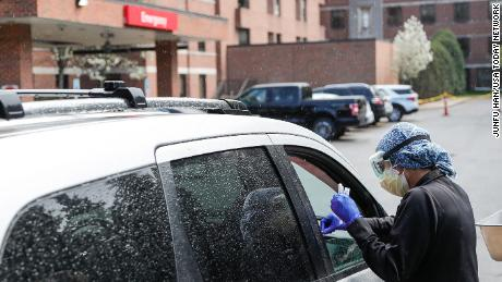 An ER technician tests patients for Covid-19 outside of the emergency entrance of Beaumont Hospital in Grosse Pointe, Thursday, April 15, 2021.