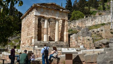 Tourists at the ancient ruins of the  Treasury of the Athenians in the Archaeological Site of Delphi  (UNESCO World Heritage Site, 1987) on April 4, 2021 in Delphi, Greece. The ruins of the archaeological site and monuments of Delphi had a great influence on the ancient world in the 6th century B.C, as evidenced by the various monuments built by most of the important ancient Greek city-states, demonstrating unity of the ancient Greek world. (Photo by Milos Bicanski/Getty Images)