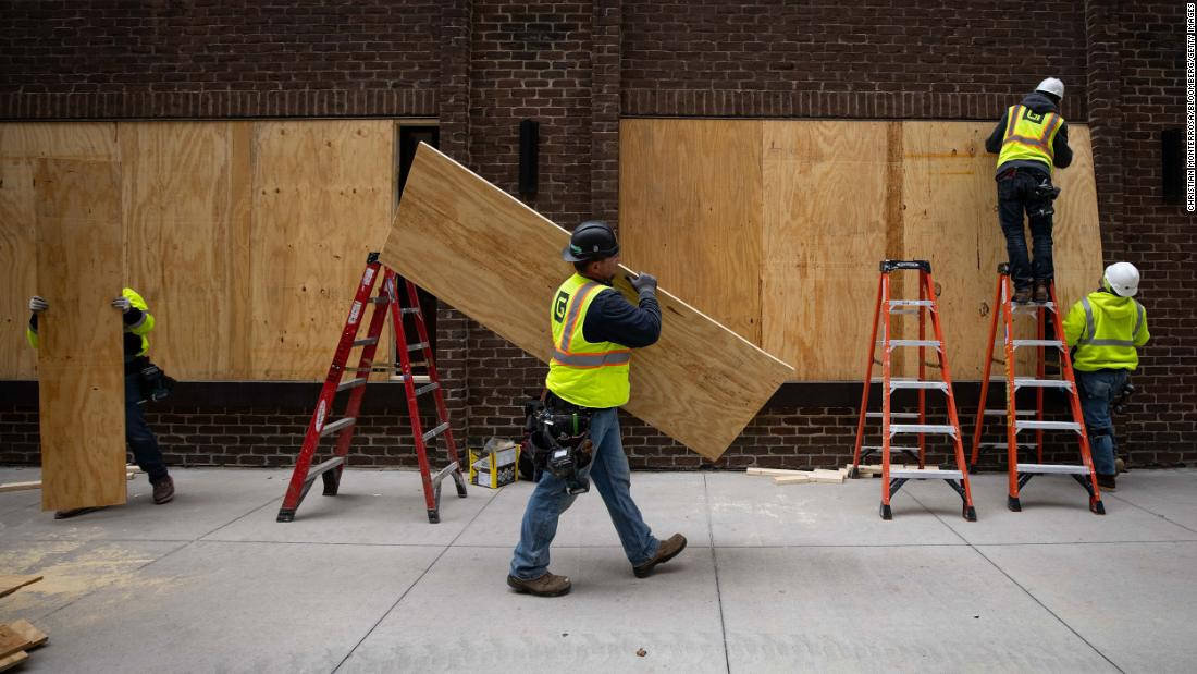 Workers board up businesses near the Hennepin County Government Center on April 20.