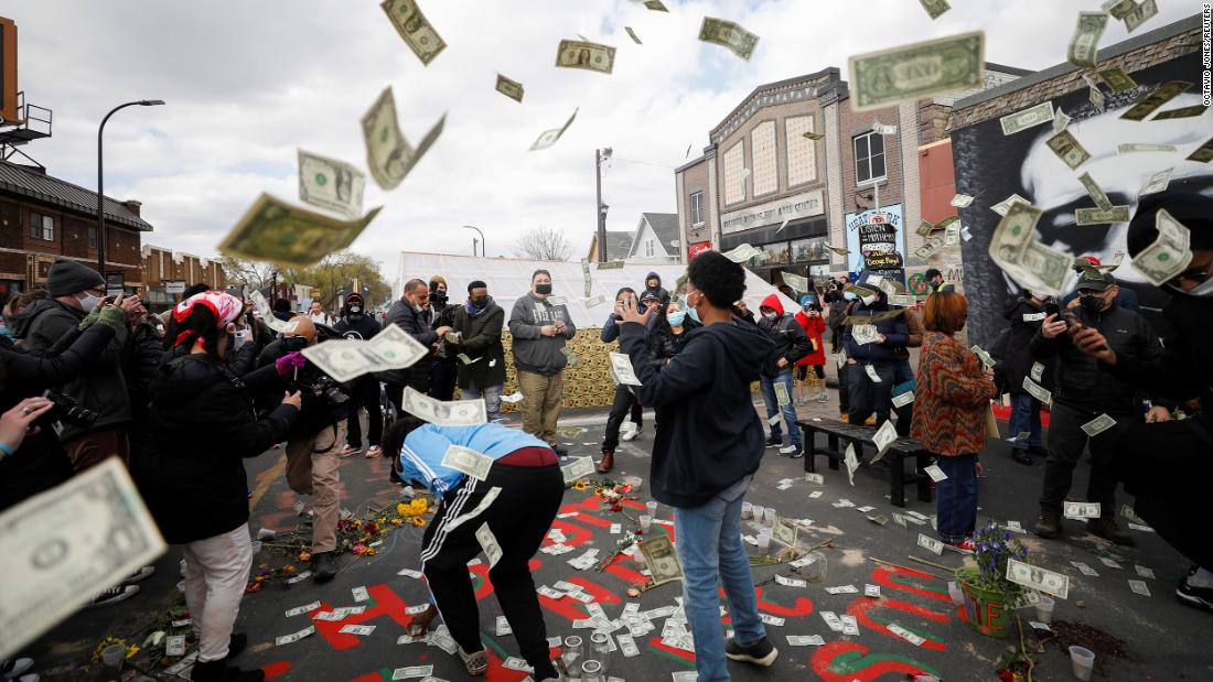 Money is tossed in the air as people celebrate the verdict at George Floyd Square in Minneapolis.