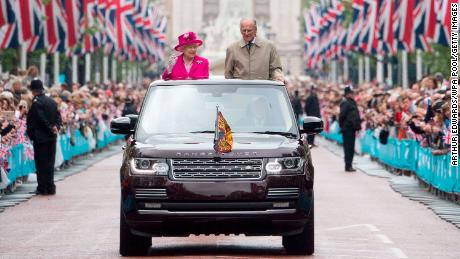 """Queen Elizabeth II and Prince Philip, Duke of Edinburgh wave to guests attending """"The Patron's Lunch"""" celebrations for The Queen's 90th birthday on The Mall on June 12, 2016."""