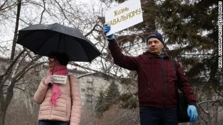 "Supporters of Alexey Navalny hold signs reading ""Freedom to Navalny"" (left) and ""Let Navalny Live"" as they take part in an unauthorized rally in Lenina Square, Novosibirsk."