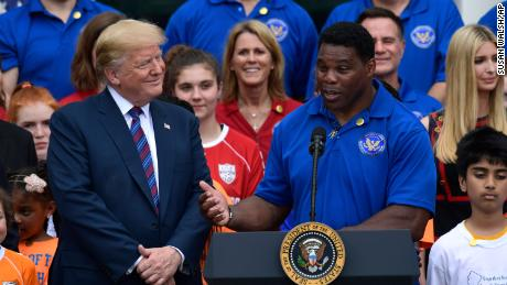Then-President Donald Trump listens as Herschel Walker speaks on the South Lawn of the White House in May 2018.