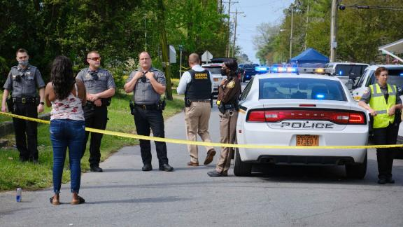 A resident, left, uses her cell phone to record video of police near the scene of a shooting, Wednesday, April 21, 2021 in Elizabeth City, N.C. At least one law enforcement officer with a sheriff's department in North Carolina shot and killed a man while executing a search warrant Wednesday, the sheriff's office said.  (Chris Day/The Daily Advance via AP)