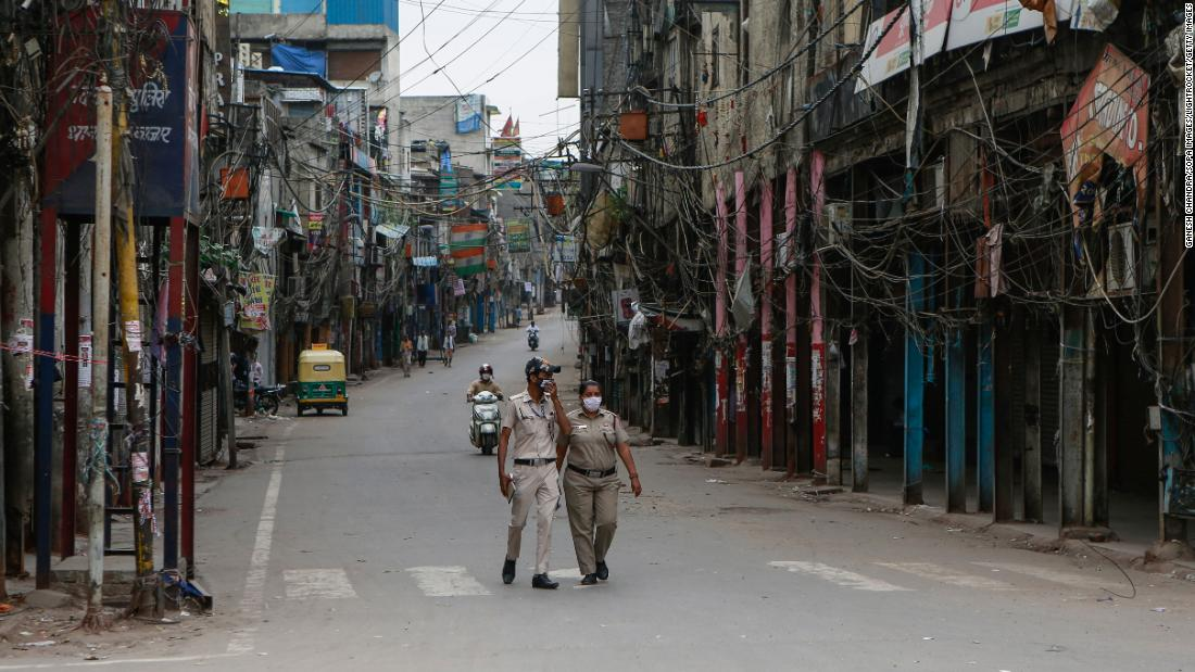 Police officers patrol a deserted street in New Delhi on April 20. The capital city has been on lockdown because of Covid-19.