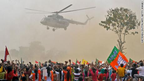Supporters of Bharatiya Janata Party (BJP) wave at a helicopter carrying Indian Prime Minister Narendra Modi upon his arrival at a rally in Kawakhali, West Bengal, on April 10.