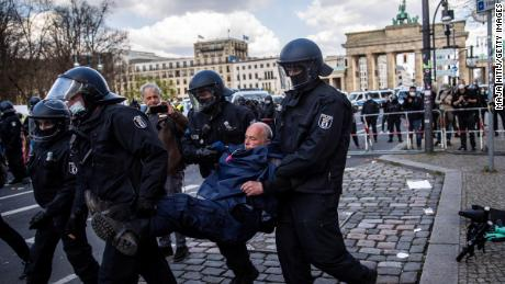 Police carry a demonstrator during protests against new legislative measures to rein in the coronavirus pandemic next to the Brandenburg Gate,  in Berlin, on April 21.