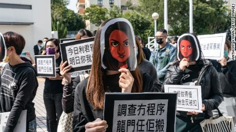 Hong Kong public broadcaster Radio Television Hong Kong (RTHK) staffers wear masks depicting the journalist Nabela Qoser during a silent protest against the management's treatment of her outside Broadcasting House on January 28, 2021 in Hong Kong.