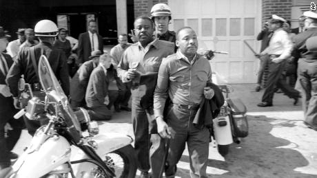 """The Rev. Ralph Abernathy, left, and the Rev. Martin Luther King Jr. are led by a policeman as they are arrested in Birmingham, Alabama on April 12, 1963. King later spent days in solitary confinement writing his """"Letter From Birmingham Jail,"""" which stirred the world by explaining why Black people couldn't keep waiting for fair treatment."""