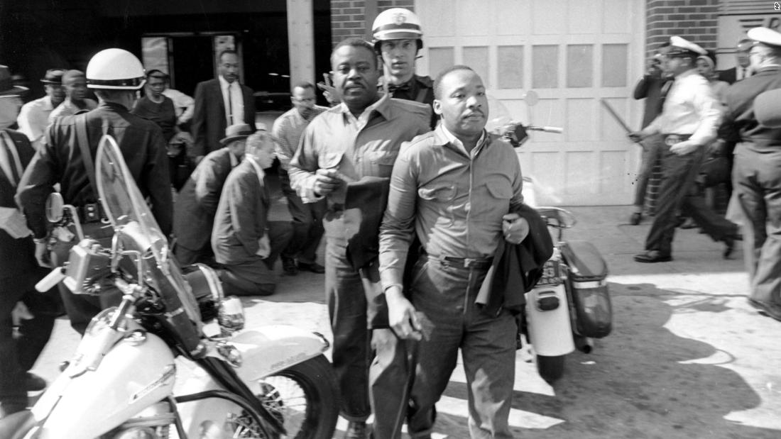"The Rev. Ralph Abernathy, left, and the Rev. Martin Luther King Jr. are led by a policeman as they are arrested in Birmingham, Alabama on April 12, 1963. King later spent days in solitary confinement writing his ""Letter From Birmingham Jail,"" which stirred the world by explaining why Black people couldn't keep waiting for fair treatment."