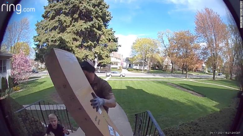 UPS driver sprints across busy street to rescue a young boy pinned under a heavy package