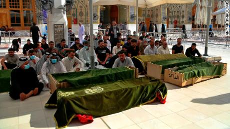 Mourners pray near the coffins of coronavirus patients killed in the hospital fire during their funeral at the Imam Ali shrine in Najaf, Iraq, on Sunday.