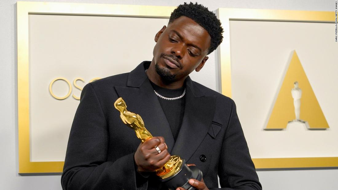"Daniel Kaluuya examines his best supporting actor Oscar, which he won for his role as Black Panther leader Fred Hampton in ""Judas and the Black Messiah."""