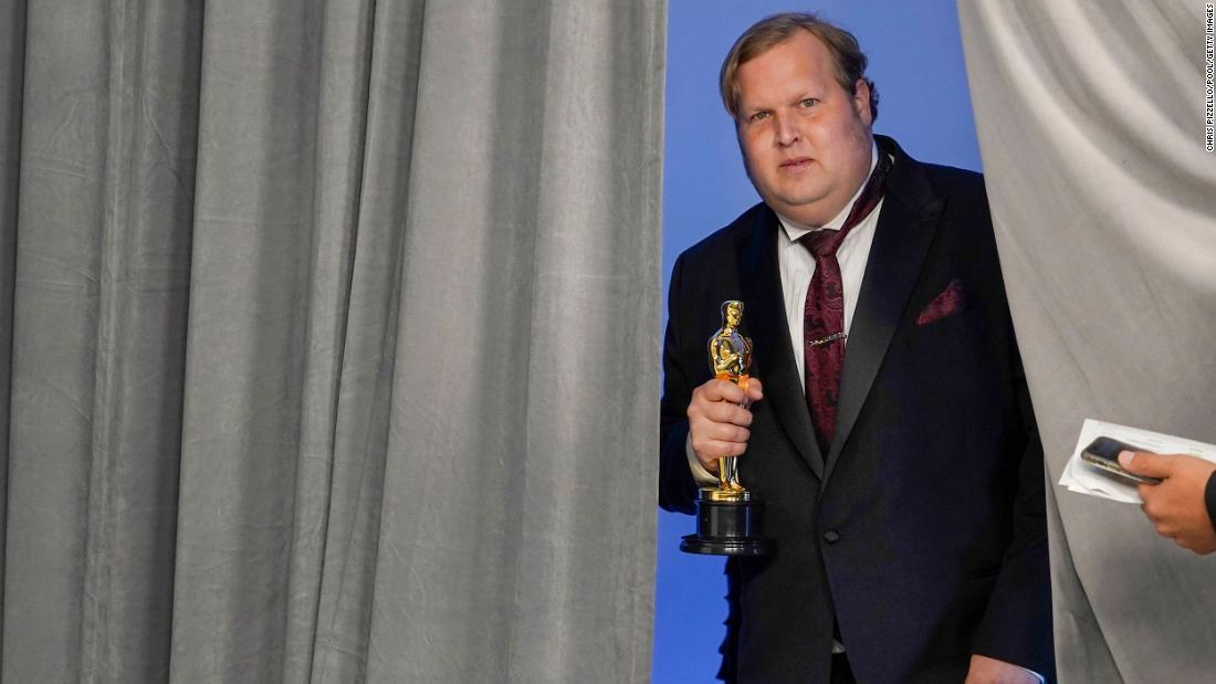 "Phillip Bladh, holding the best sound Oscar for ""Sound of Metal,"" enters the press room in Los Angeles."