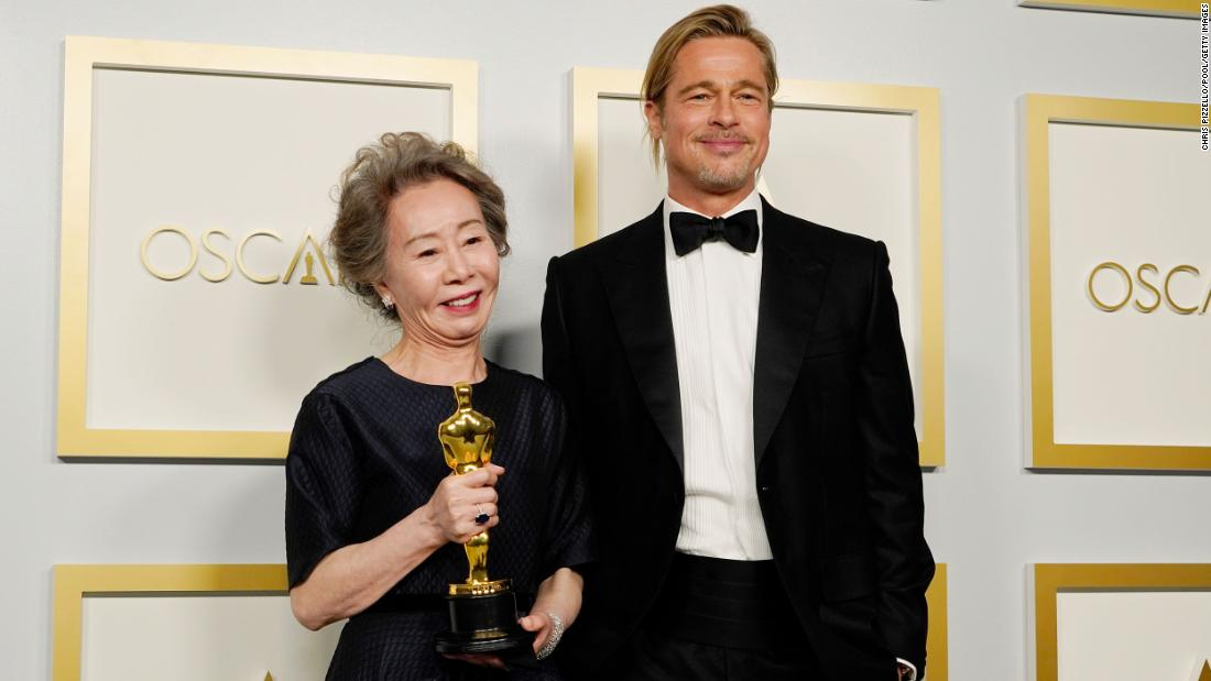 Yuh-jung Youn holds her best supporting actress Oscar as she stands next to presenter Brad Pitt in the press room.