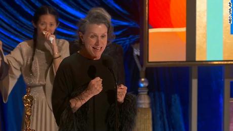 """Frances McDormand accepts the best picture award for """"Nomadland"""" as director Chloe Zhao looks on at the Oscars on Sunday, April 25, 2021."""