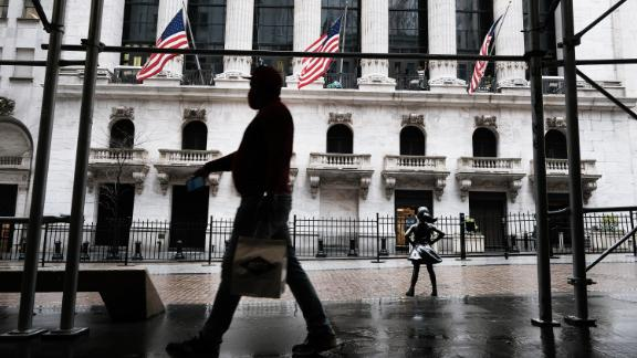People walk by the New York Stock Exchange on April 15, 2021 in New York City. After major companies reported strong earnings and new economic data points to a rebound in consumer spending, U.S. stocks climbed to record levels on Thursday.