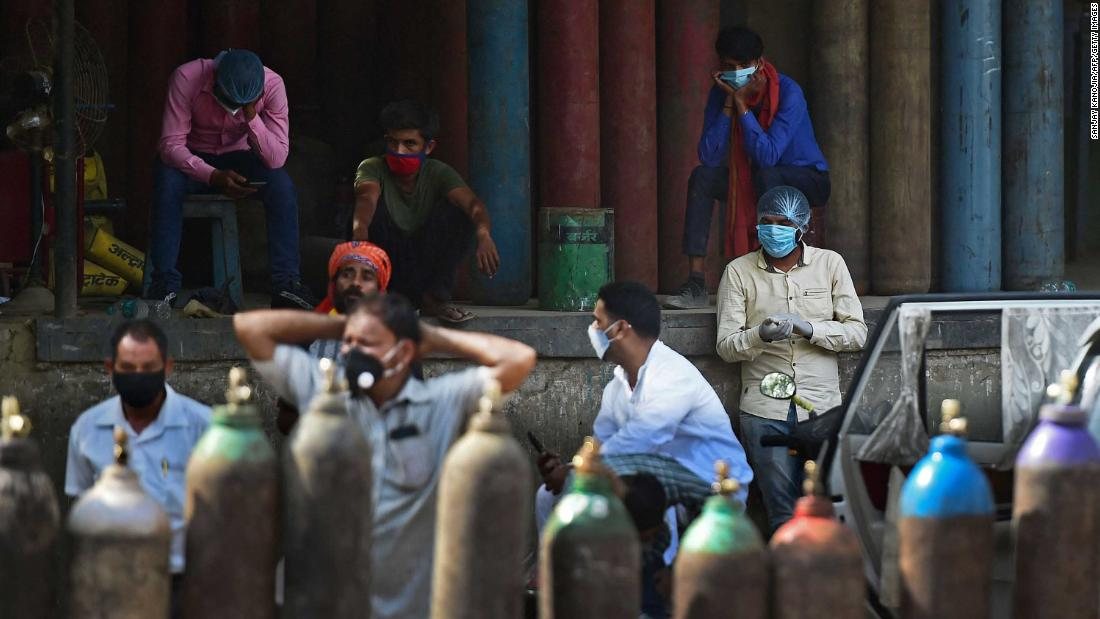 People wait to refill their oxygen cylinders at a refilling station in Allahabad on Saturday, April 24.
