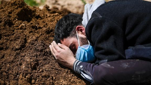 Umar Farooq mourns at the grave of his mother, a Covid-19 victim, in Srinagar.