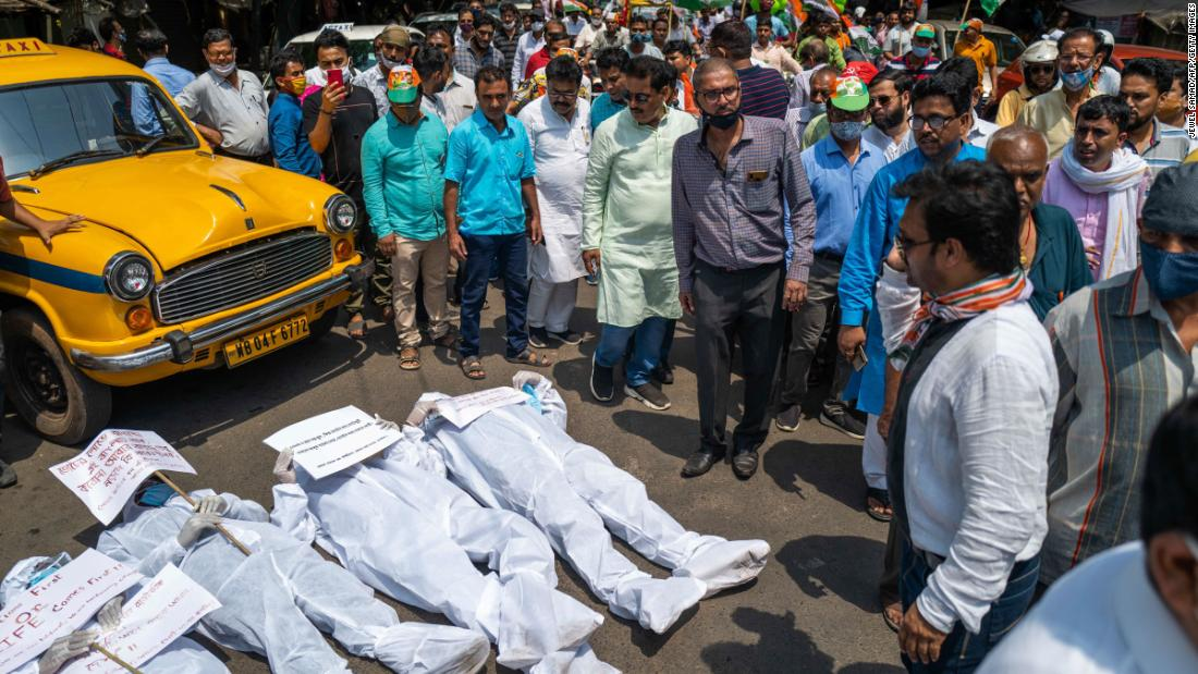 Protesters wearing protective suits lie on a street near the Election Commission office in Kolkata on April 7. They were calling for a stop to the ongoing state legislative election and its associated campaign rallies.
