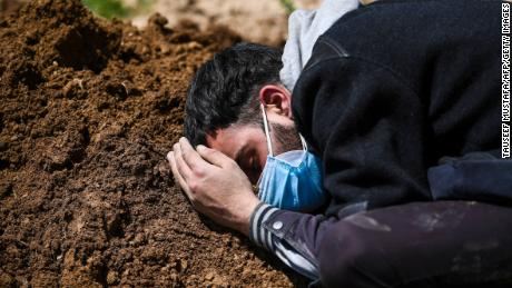 Umar Farooq mourns at the grave of his mother, who died of Covid-19 coronavirus, after her burial at a graveyard in Srinagar on April 26, 2021. (Photo by Tauseef MUSTAFA / AFP) (Photo by TAUSEEF MUSTAFA/AFP via Getty Images)