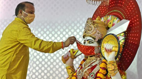 A Hindu priest puts a face mask on an idol of the Goddess Ashapura during Navaratri celebrations in Beawar on April 13.