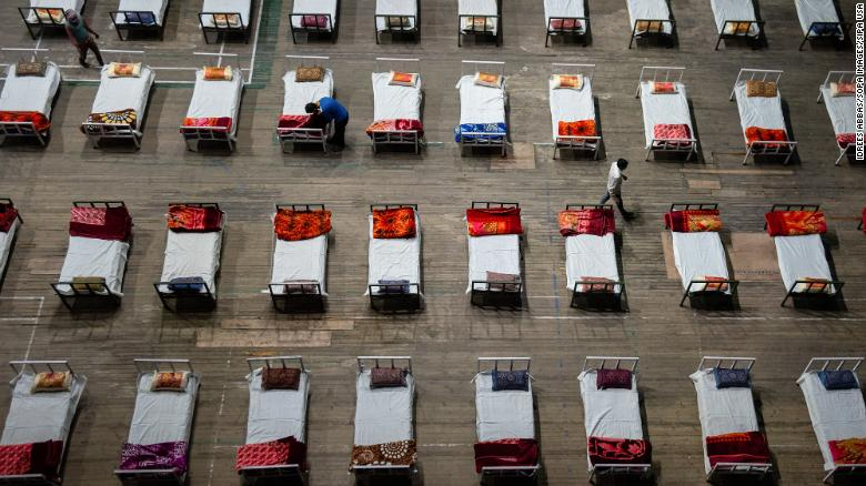 Workers prepare beds to set up a Covid-19 isolation center inside a sports stadium in Srinagar, India, on April 27.