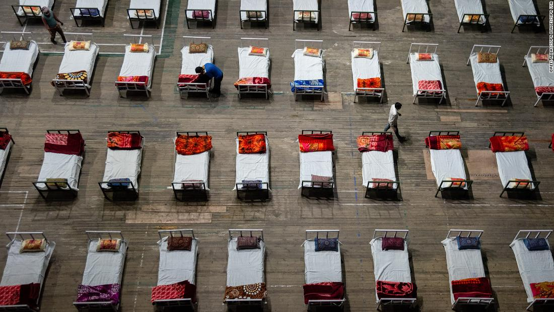 Workers prepare beds for a Covid-19 isolation center that was set up inside a stadium in Srinagar on Tuesday, April 27.