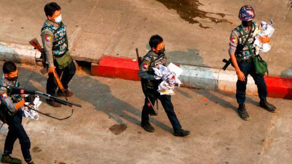 Police officers clear a road after demonstrators spread placards in Yangon on Saturday, April 24.