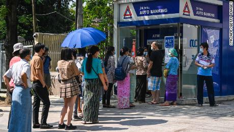 People queue as they wait to use the ATM in Yangon on April 7, 2021, amid strained banking operations due to the military coup.