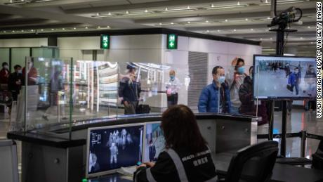 Flyplasshelsearbeidere overvåker kroppstemperaturen til passasjerer som ankommer med varmeskannere i en ankomsthall på Hong Kong internasjonale lufthavn 21. februar 2020.