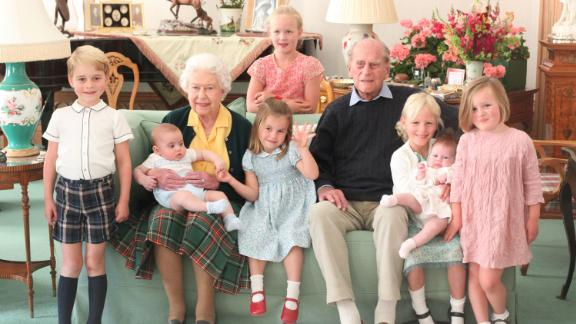 Queen Elizabeth II and Prince Philip pose with seven of their great-grandchildren in this photo taken in 2018. The children, from left, are Prince George, Prince Louis, Princess Charlotte, Savannah Phillips, Isla Phillips, Lena Tindall and Mia Tindall.