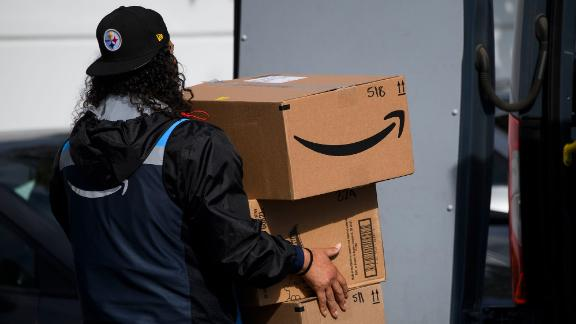 An Amazon.com Inc. delivery driver carries boxes into a van outside of a distribution facility on February 2, 2021 in Hawthorne, California. Jeff Bezos said February 1, 2021, he would give up his role as chief executive of Amazon later this year as the tech and e-commerce giant reported a surge in profit and revenue in the holiday quarter. The announcement came as Amazon reported a blowout holiday quarter with profits more than doubling to $7.2 billion and revenue jumping 44 percent to $125.6 billion. (Photo by Patrick T. Fallon/AFP/Getty Images)