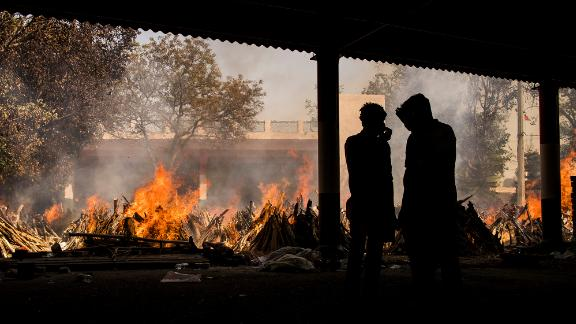 People are silhouetted against multiple burning funeral pyres of patients who died of the Covid-19 on April 24, 2021 in New Delhi, India.
