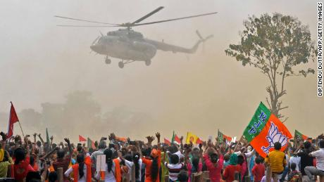 Supporters of Bharatiya Janata Party (BJP) wave towards a helicopter carrying Indian Prime Minister Narendra Modi upon his arrival at a public rally at Kawakhali on the outskirts of Siliguri on April 10, 2021.