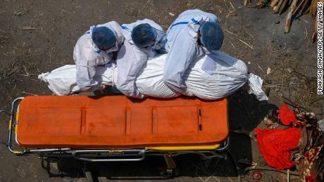 2021年4月27日、ニューデリーの火葬場で家族と救急車のスタッフが保護具を着用してコロナ19で死亡した被害者の遺体を携帯しています。