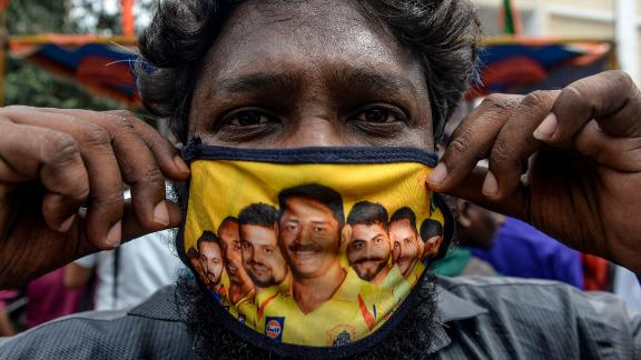 A man shows his facemask decorated with portraits of Chennai Super Kings cricket captain Mahendra Singh Dhoni (C) and other team players as Covid-19 coronavirus cases continue to rise in the country, in Chennai on September 16, 2020. (Photo by Arun SANKAR / AFP) (Photo by ARUN SANKAR/AFP via Getty Images)