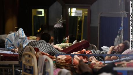 Covid-19コロナウイルスの患者は、2021年4月29日、ニューデリーのCovid-19コロナウイルス病棟に一時的に改造された宴会場で休息を取っています。