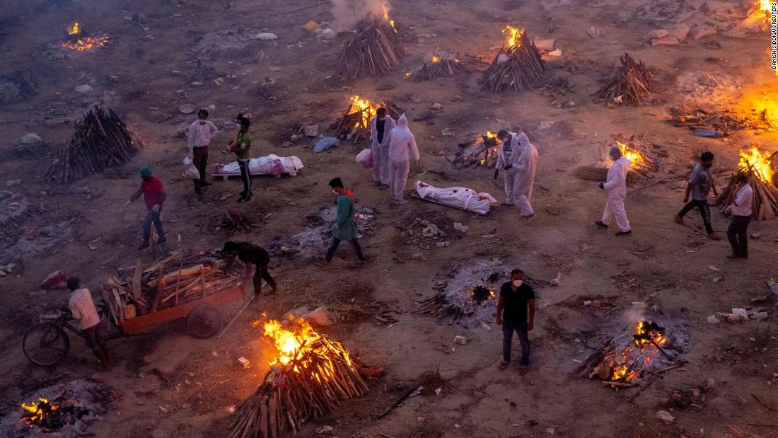 Funeral pyres burn in New Delhi as people wait to cremate Covid-19 victims on Friday, April 23. A second wave of Covid-19 is devastating India, killing thousands of people each day and setting world records for daily infections.
