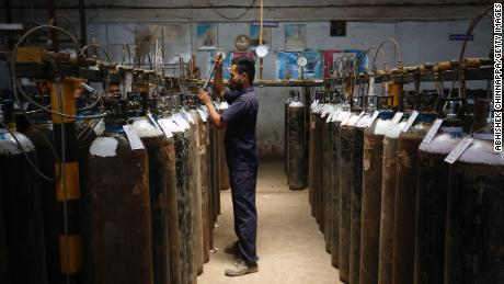 An employee fills oxygen cylinders inside an oxygen filling centre on April 28, 2021 in Bengaluru, India.