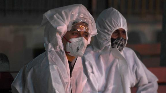 People wear protective suits while watching a relative's cremation in New Delhi on April 28. Their loved one died from Covid-19.