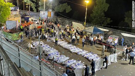 Los oficiales de seguridad y los rescatistas israelíes rodean los cuerpos de las víctimas que murieron durante la noche en el monte Meron.