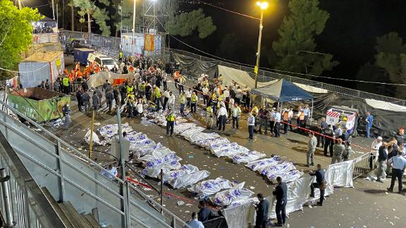 Israeli security officials and rescuers stand around the bodies of victims who died overnight on Mount Meron.