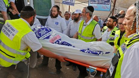 Los equipos de rescate israelíes llevan un cuerpo a una ambulancia el viernes en Mount Meron.