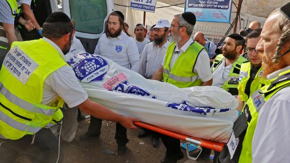 Israeli rescue teams carry a body into an ambulance on Friday at Mount Meron.